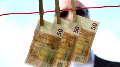 stock-footage-a-man-in-a-suit-remove-banknotes-from-a-clothesline-usable-for-greedy-managers-any-dirty-money